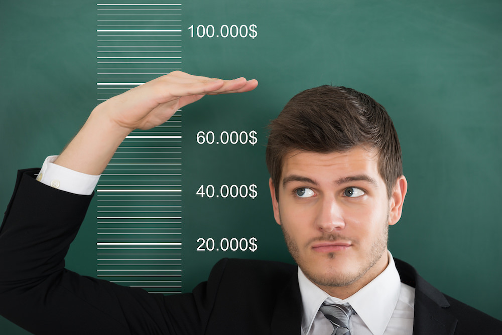 Close-up Of A Young Businessman Comparing His Salary With Profit